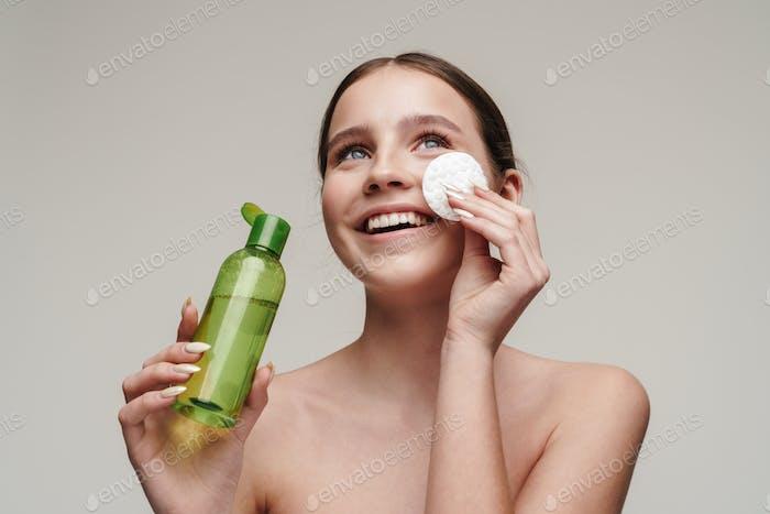 Bild von zufriedenen jungen Shirtless Frau mit Gesichtslotion und Lächeln