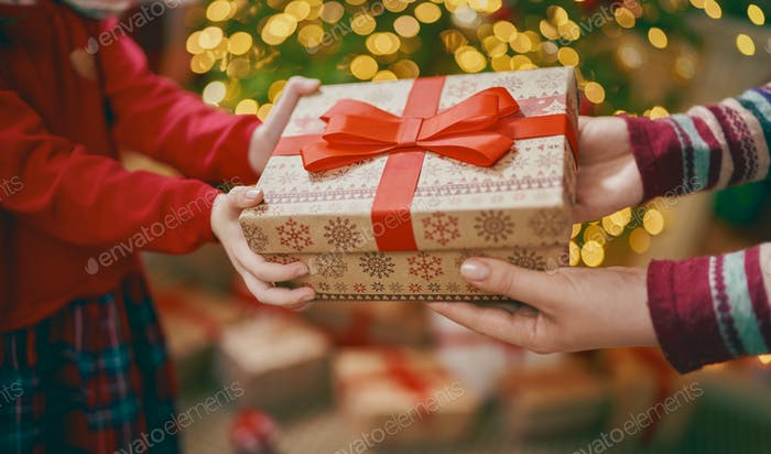 Hands of parent giving a x-mas gift to child.