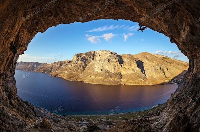 Männliche Kletterer klettern auf dem Dach in der Höhle vor Sonnenuntergang