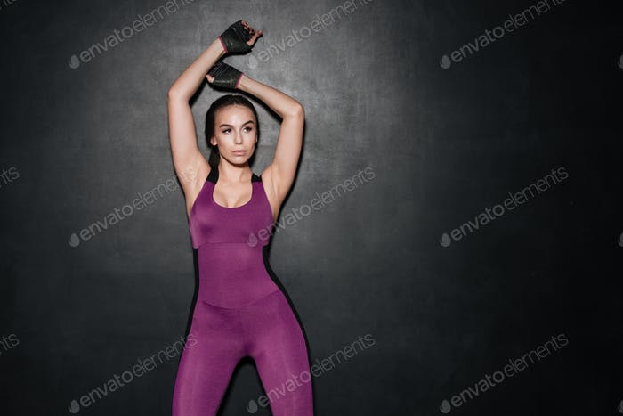 Strong sportswoman posing over grey background.
