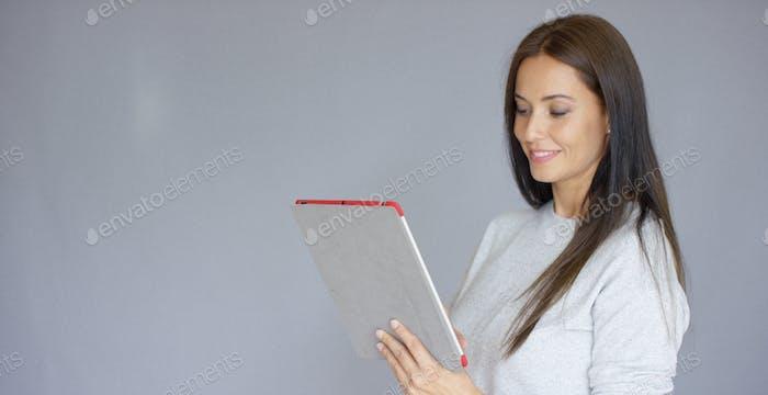 Schöne Frau mittleren Alters mit Tablet-Computer
