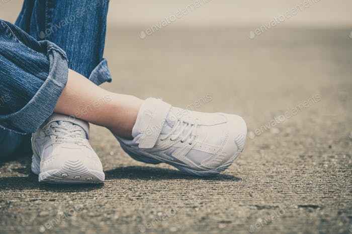 youth sneakers on girl legs on road