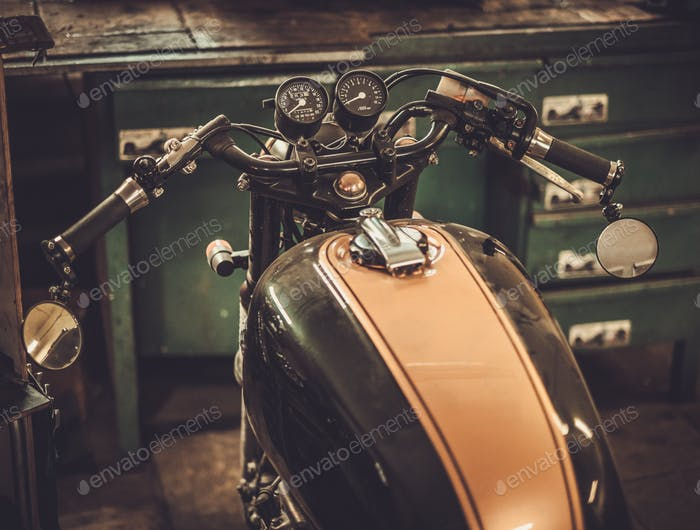 Vintage style cafe-racer motorcycle in customs garage