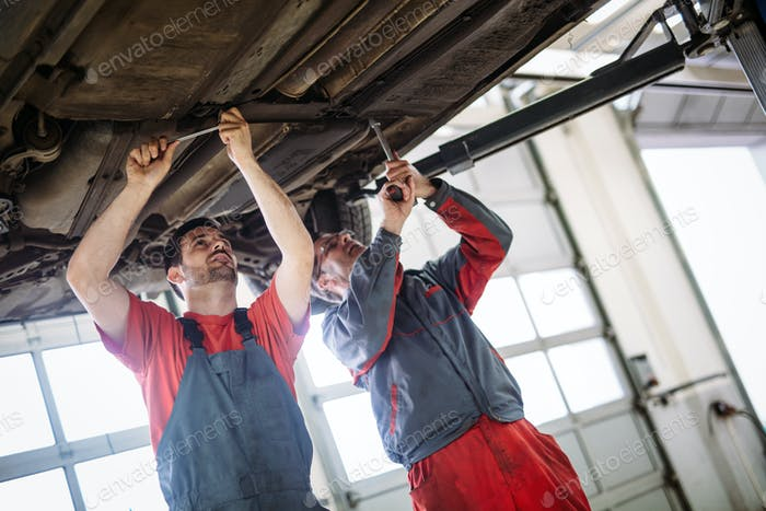 Two mechanics in uniform are working in auto service with lifted vehicle