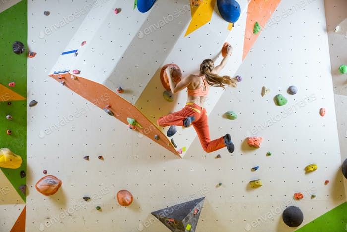 Young woman jumping on handhold in bouldering gym