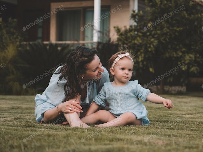 Young mother with her daughter play sitting on a lawn in summer day