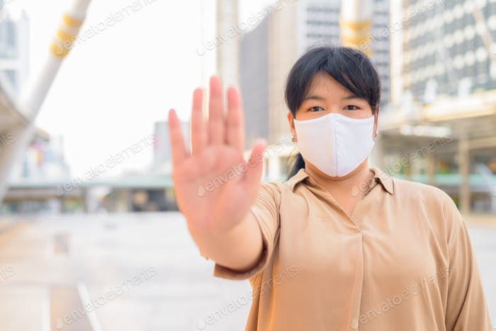 Overweight Asian woman with mask showing stop gesture in the city
