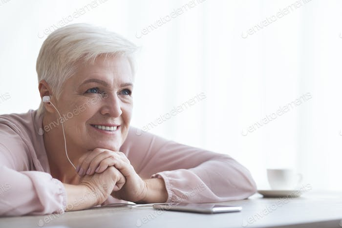 Dreamy senior lady listening to music, using phone