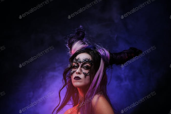 Young woman wearing banshee dark make-up and violet horns posing in a studio with smke