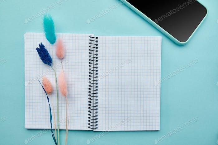 Notizblock und Telefon auf blauem Hintergrund geöffnet