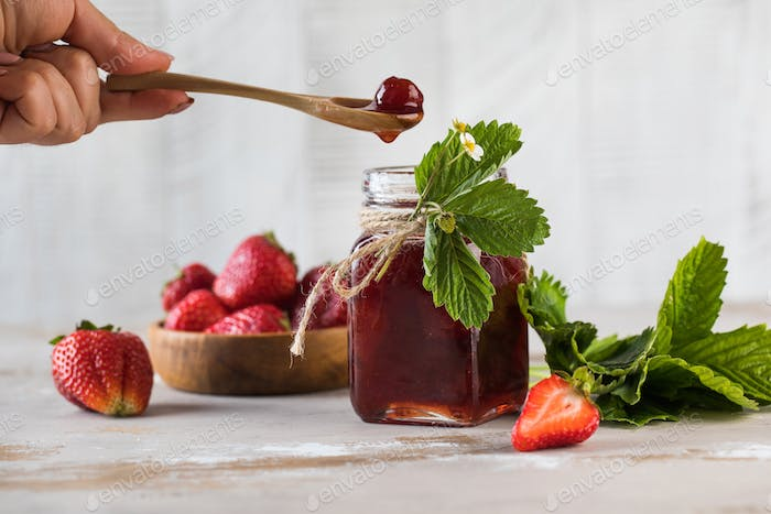 Strawberry jam in a jar, fermented strawberries in a wooden spoon. Fermented berries.