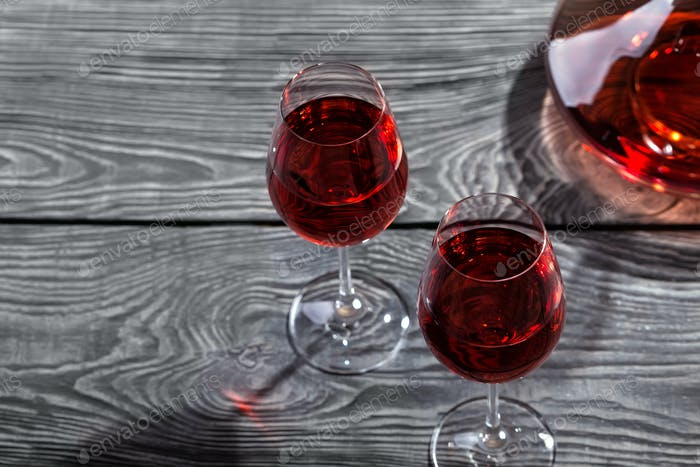 Decanter and two glasses of red wine on a wooden table