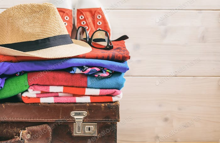 Travel accessories on a suitcase and white background - copy space
