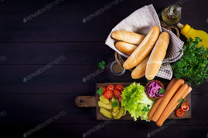 Ingredients for hot dog with  sausage, pickled cucumber, tomatoes, red onions