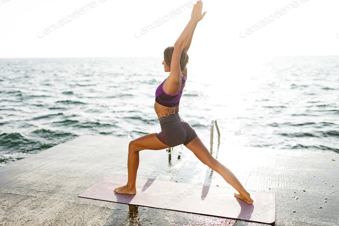 Beautiful lady in sporty top and shorts practicing yoga with amazing sea view on background
