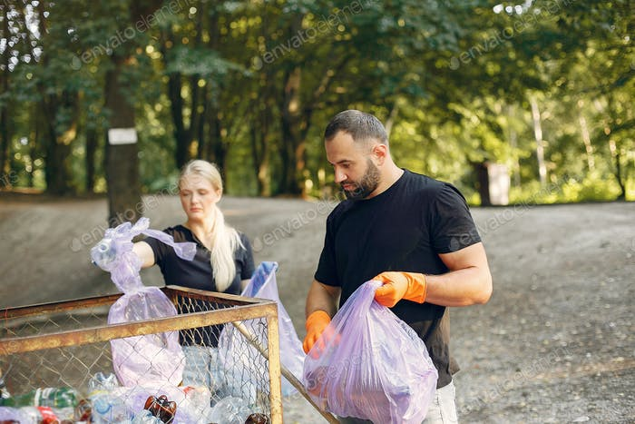 Couple collects garbage in garbage bags in park