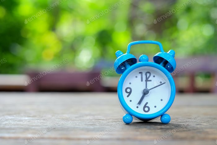 Seven o'clock,Blue alarm clock on wooden with green blurred back