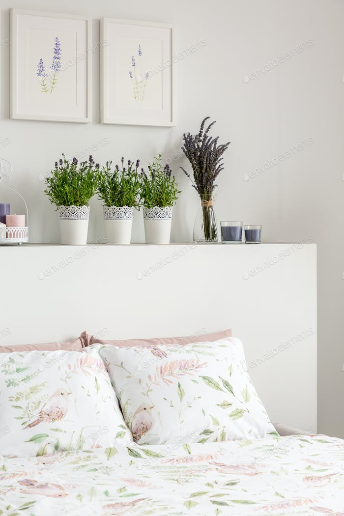 Lavender flowers on headboard of bed with pillows in white bedro