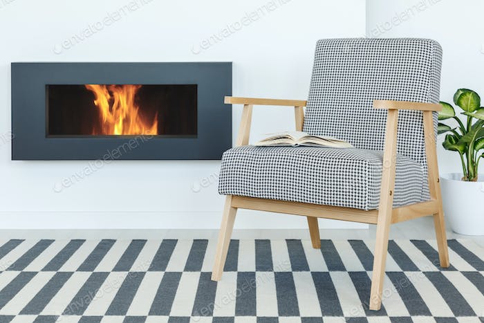 Retro armchair with a book next to a fireplace set on a striped