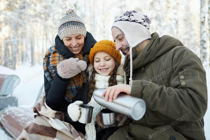 Family Drinking Cocoa in Park