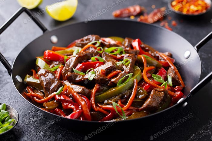 Beef and Vegetables Stir Fry in a Pan. Dark Background. Close up.