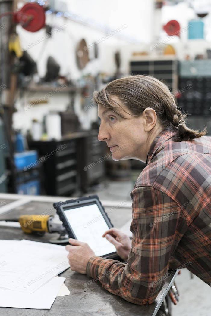 Side view of blond woman wearing checkered shirt standing at workbench in metal workshop, holding