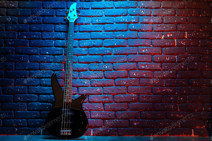 Electric guitar in neon light against dark walll