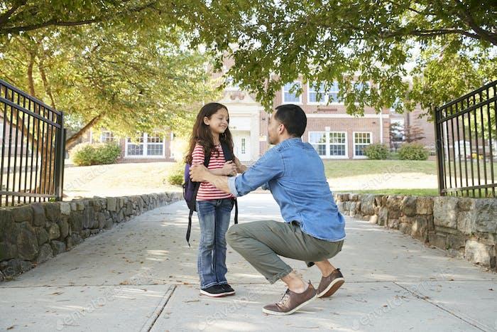 Vater Dropping Off Tochter vor der Schule Tore