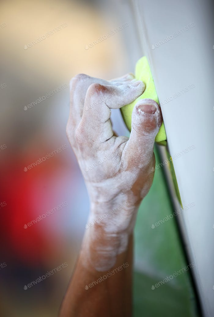 Closeup of man's hand on handhold on artificial climbing wall
