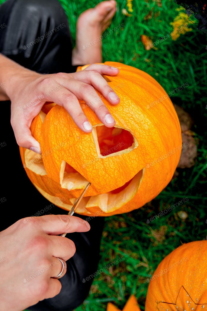 A close up of man's hand who cuts with knife a pumpkin