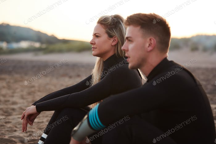 Profile View Of Couple Wearing Wetsuits On Surfing Staycation Sitting On Beach Looking Out To  Sea