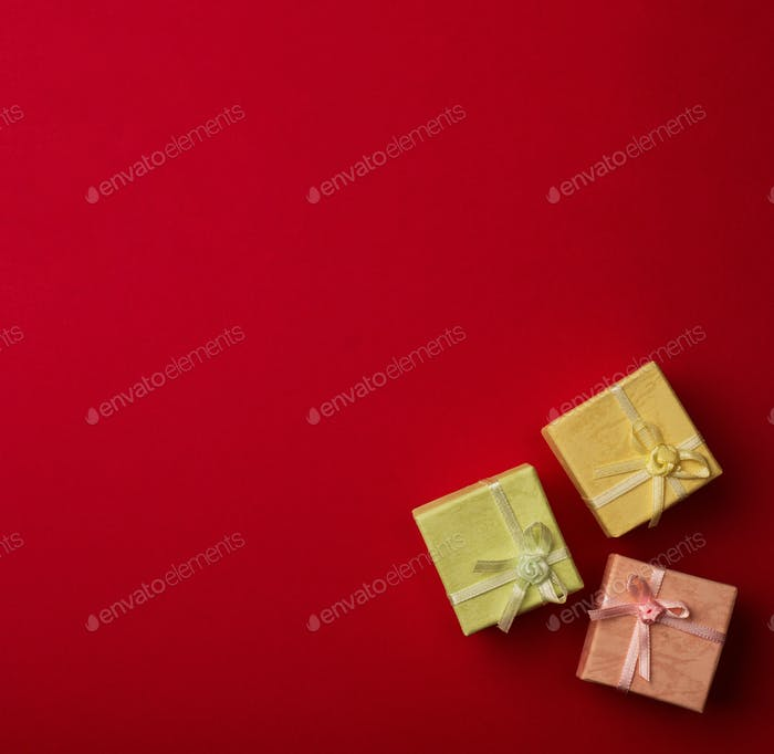 Three small gift boxes with ribbons on red background