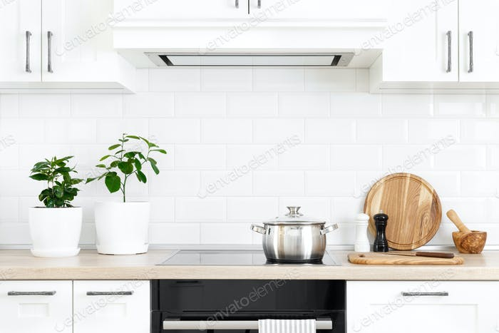 White modern kitchen interior with wooden worktop and kitchenware, culinary concept, background