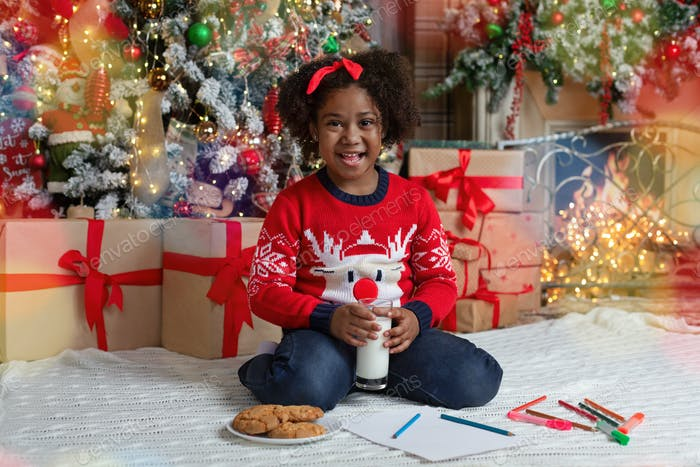 Cute afro girl drinking milk and eating cookies near Christmas tree