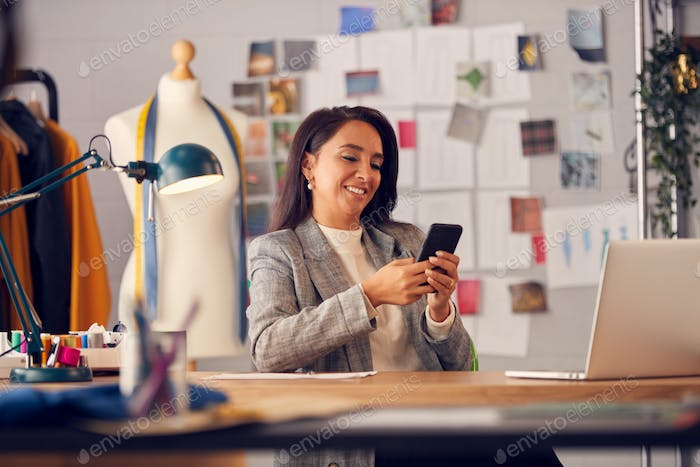Differential Focus Shot Of Female Fashion Designer Using Mobile Phone To Browse Internet At Desk