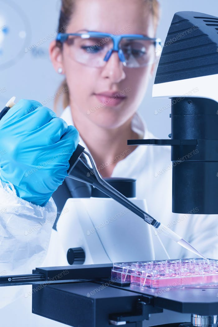 Female scientist with microscope, holding micro pipette