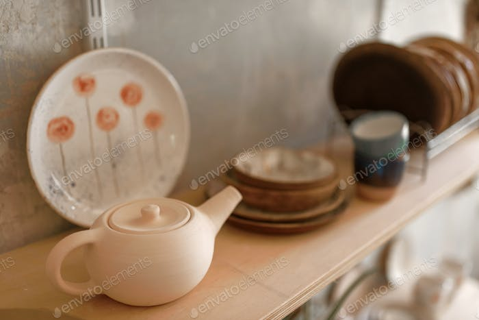 Clay dishware on shelf in pottery workshop, nobody