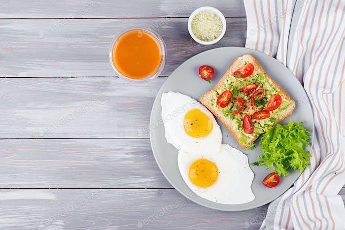 Frühstück. Spiegelei, Gemüsesalat und ein gegrilltes Avocado-Sandwich auf grauem Hintergrund. Ansicht von oben