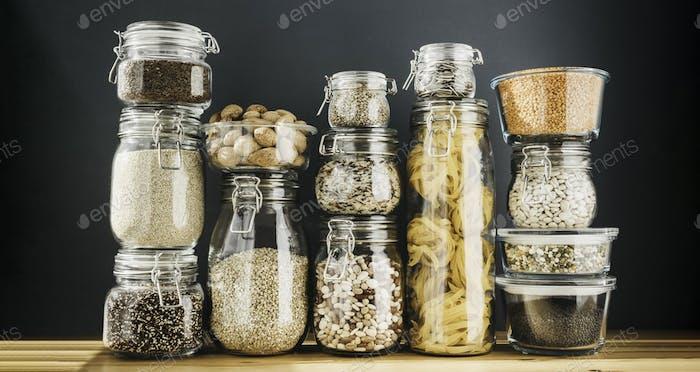 Sortiment von ungekochten Körnern, Getreide und Nudeln in Gläsern auf Holztisch. Gesundes Kochen