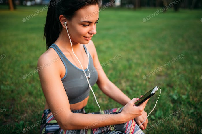 Woman in headphones sitting on grass and relax