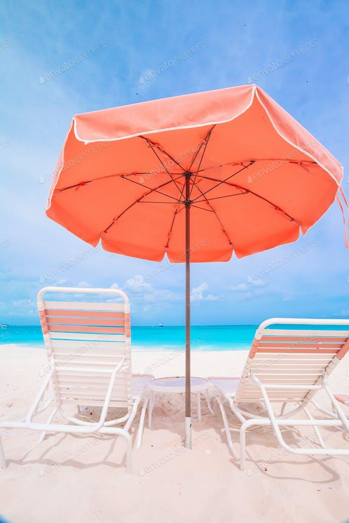 Sonnenliegen und Sonnenschirme am weißen Strand am Meer