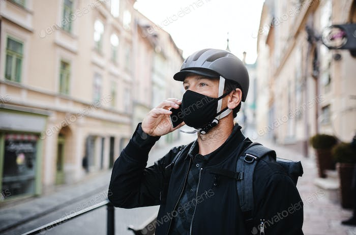 Delivery man courier with face mask and smartphone delivering parcels in town