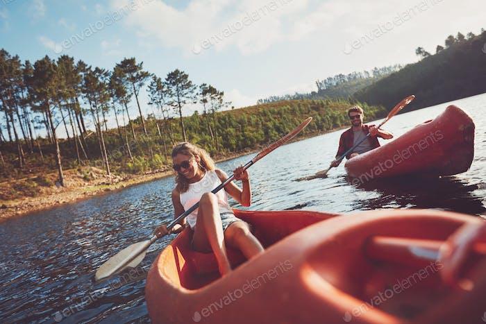Happy young couple canoeing on lake