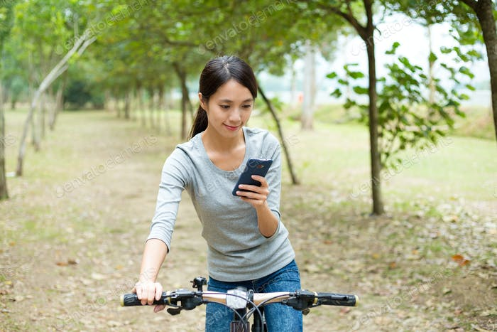 Woman use of the mobile phone for looking into the map