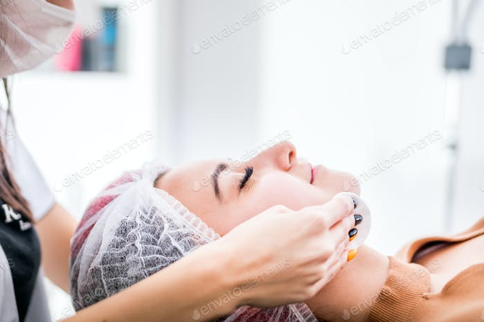 Beautician cleanses skin woman with sponge in spa beauty salon. cosmetology treatment skincare face