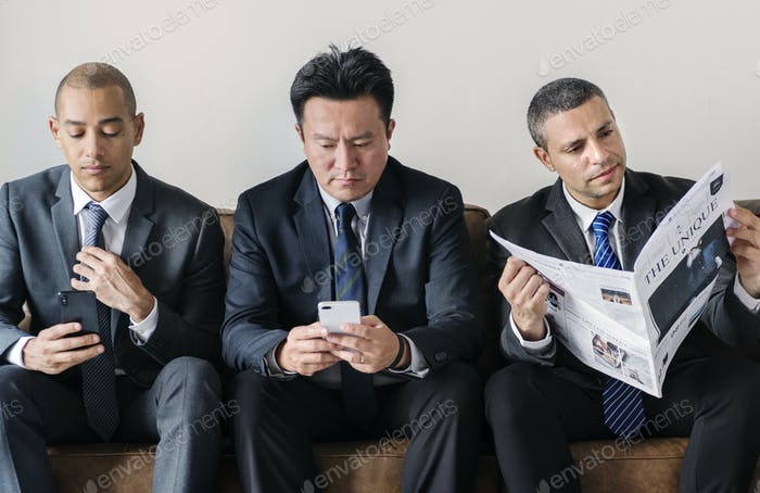 Businessmen working on phone and reading newspaper