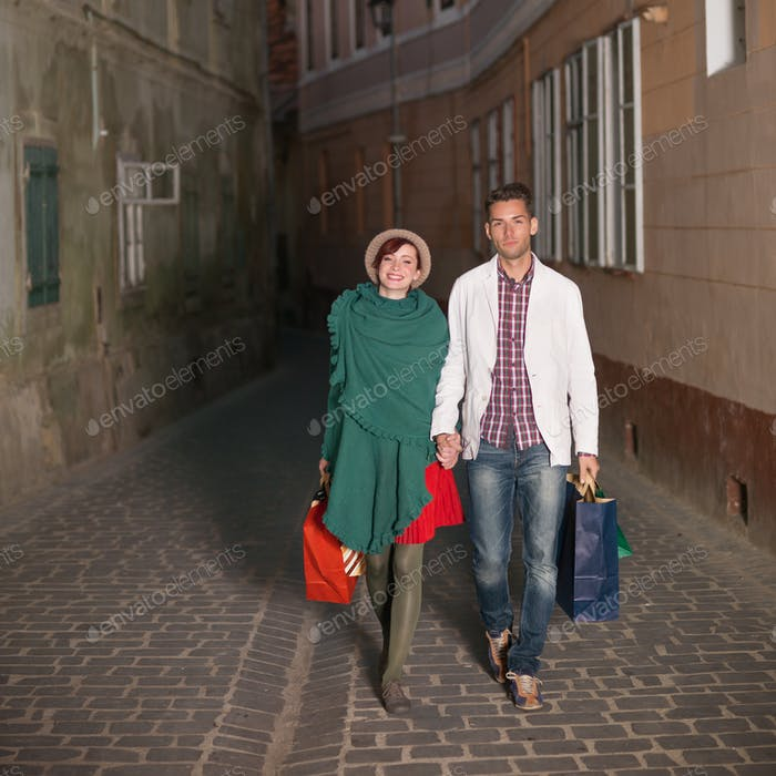 happy couple walking with shopping bags