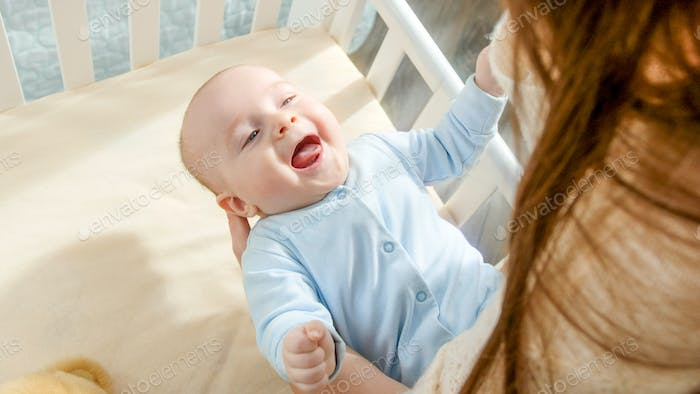 Happy smiling baby boy looking at mother rocking him in cradle. Concept of parenting, family