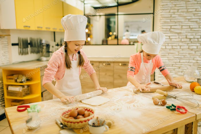 Little girls chefs with rolling pins, funny bakers