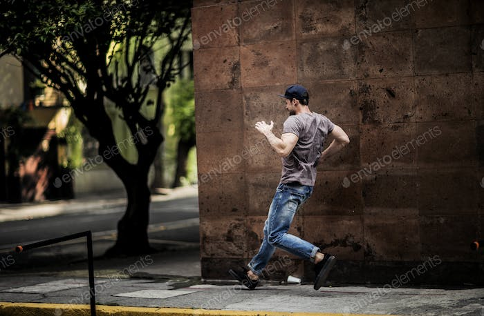 A man dancing on a city sidewalk.